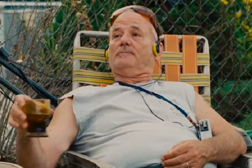 man sitting in lawn chair holding drink