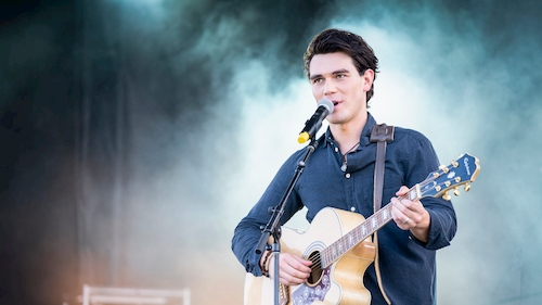 man playing guitar stage