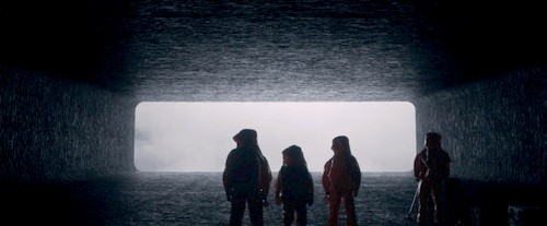 humans standing in front of foggy light in tunnel