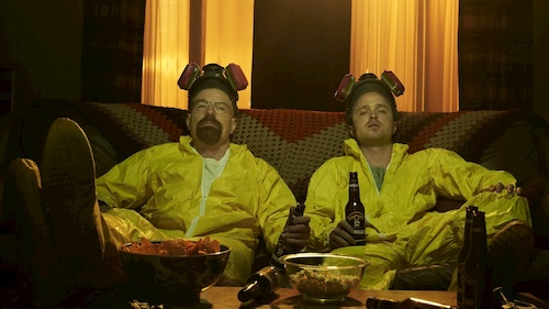 two men sitting in yellow hazmat suits on couches