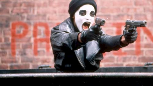 a person in white face paint pointing guns and yelling