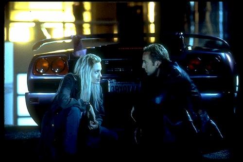 man and woman talking behind car