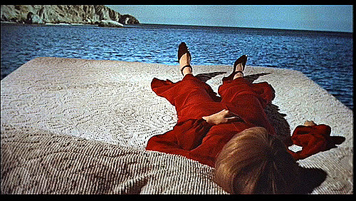 woman in red laying on bed in sea