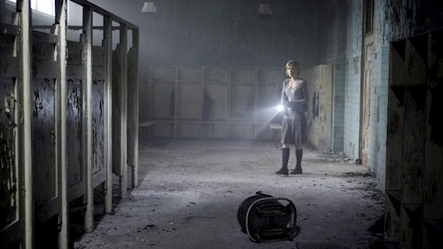 woman standing in abandoned bathroom with flashlight