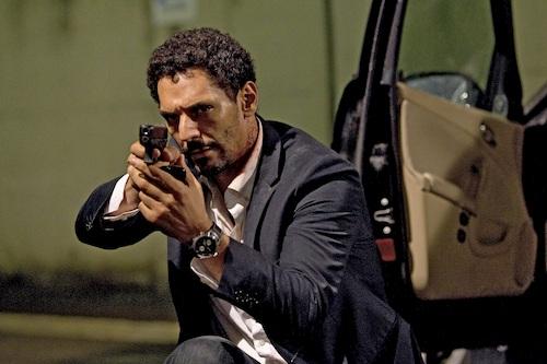 man next to car holding gun