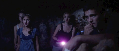 four people in a cave with a light