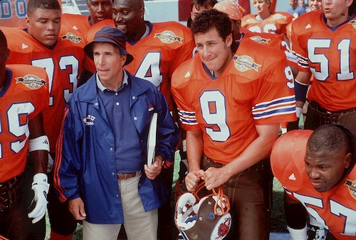 football team in orange with coach in blue