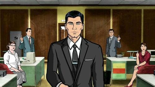man walking through office in black suit