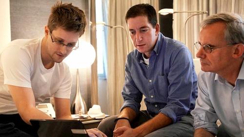 man showing computer screen to two men