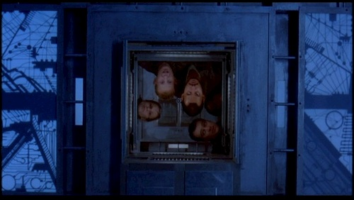 four people staring into cube window