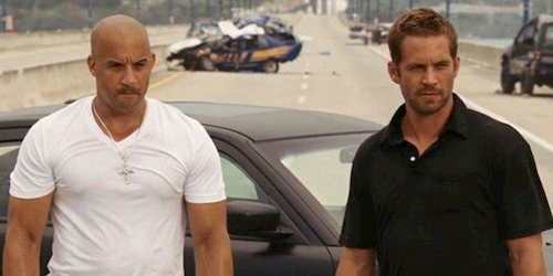 two men standing in front of cars
