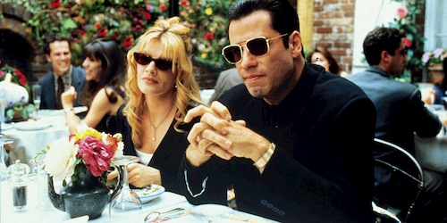 man and woman at lunch table in black suits and sunglasses