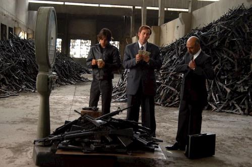 men standing next to piles of guns