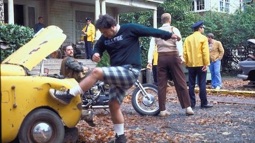 man kicking yellow car