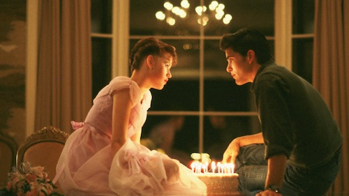 girl sitting with boy with birthday cake between them
