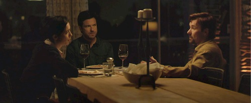 two men and woman sitting at dinner table talking