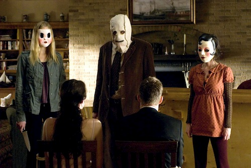 three people with masks standing talking to two sitting people