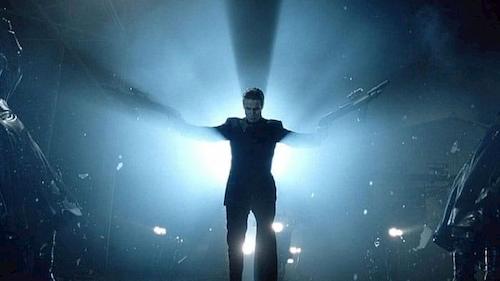 man holding guns against bright light