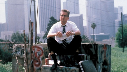 man sitting with no shoes in front of city buildings