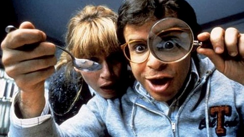 man looking under magnifying glass with woman
