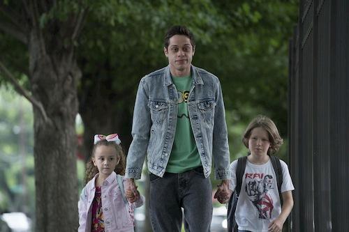 guy in jean jacket walking kids down the street