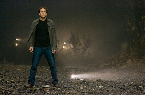 man standing in dark field staring ahead