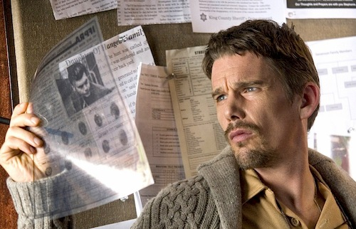 man looking at old newspaper