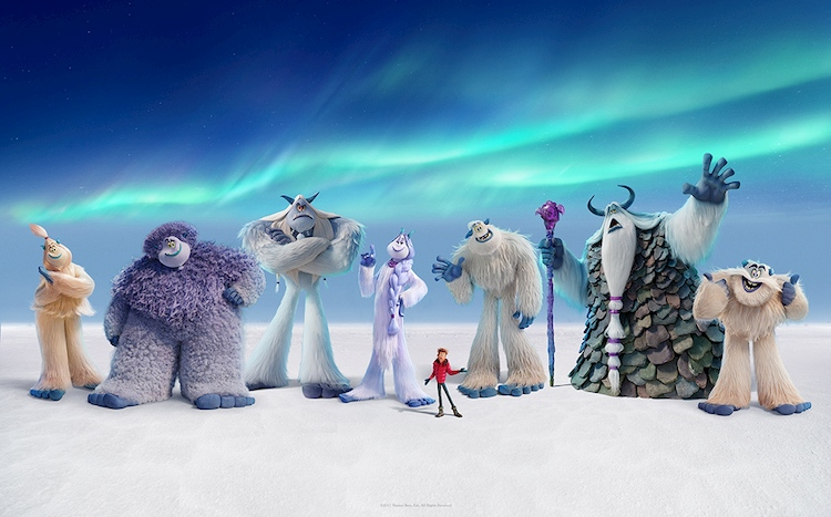 Group of animated yetis and human standing in snow
