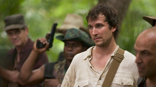 man standing in jungle with armed guys in background