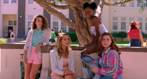 girls in bright colors sitting under tree at school
