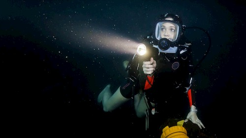 woman under water with flashlight