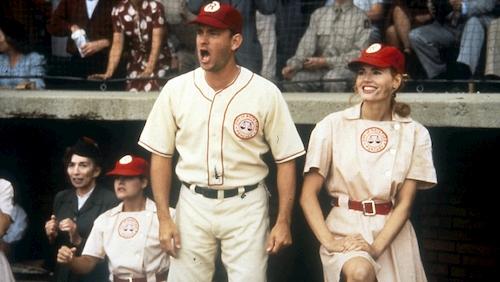 Man and woman in baseball uniforms at baseball game