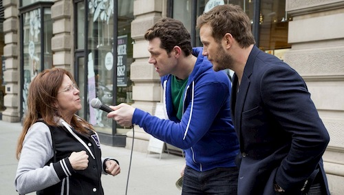 two men talking to woman on the street