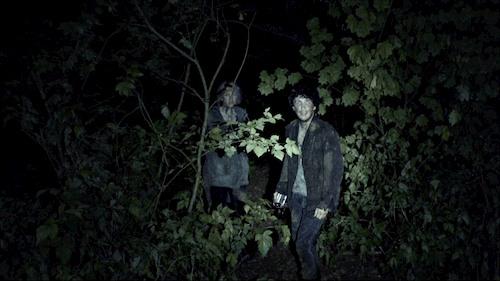 two people standing in dark woods