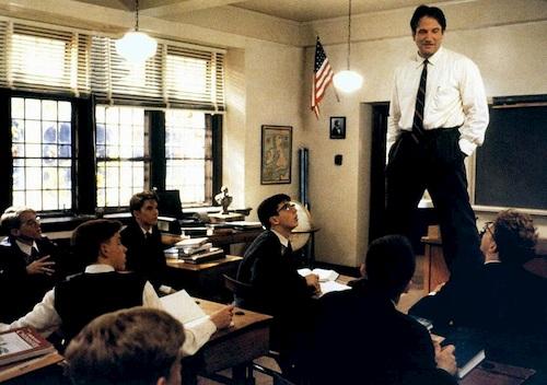 man standing on desks in class