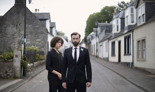 man and woman standing in suburban street