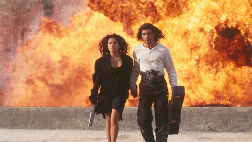 man and woman walking in front of explosion