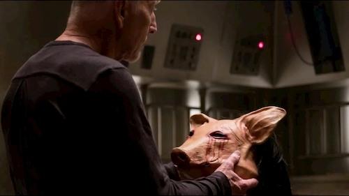 man holding rubber pig mask