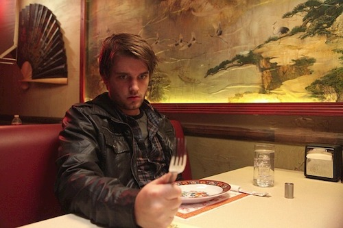 Man holding a fork at table