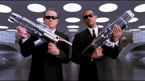 two men holding big guns