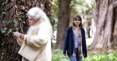 woman in woods watching elderly movie
