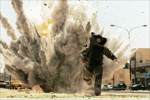man in bomb suit running from explosion