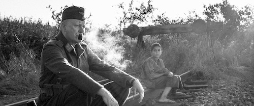 man smoking pipe sitting with boy in black outside in black and white