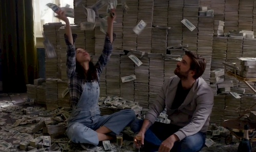 man and woman sitting in room filled with cash