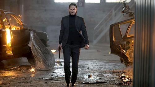 man in black walking away from broken cars with gun