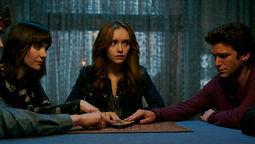 three people sitting at table with ouija board