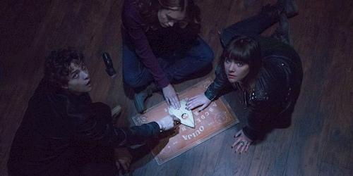 three kids using ouija board on the floor