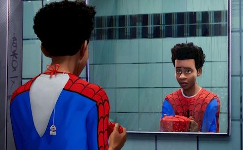 boy in spiderman costume looking into mirror