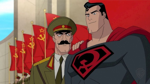 two men in uniform and costume standing in front of red flags