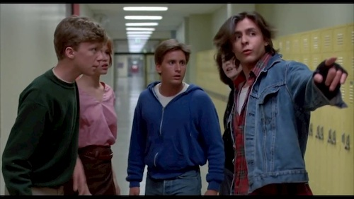 group of teenagers standing in school hallway talking